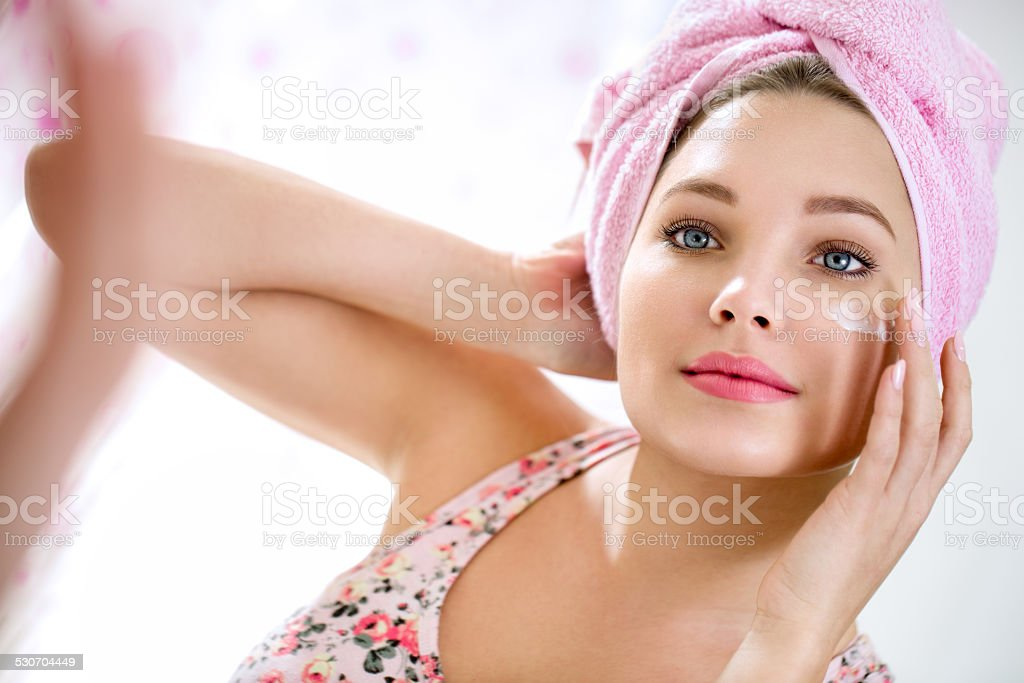 Young girl putting cream on her face stock photo