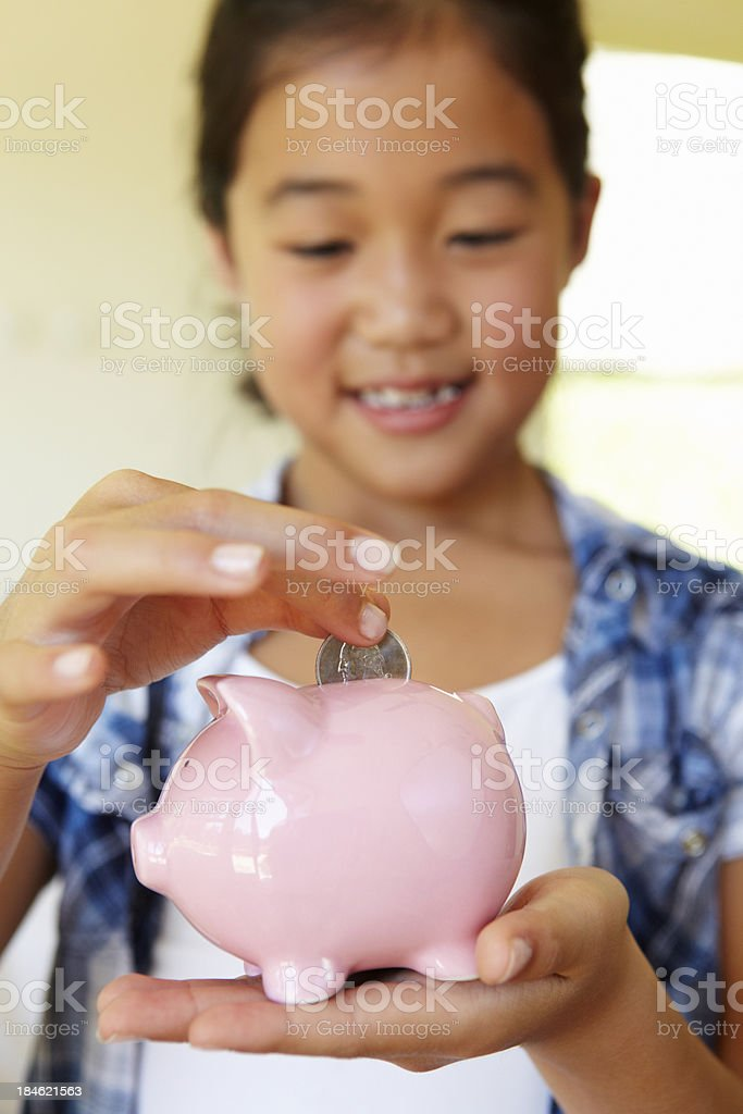 Young girl putting money in piggybank stock photo