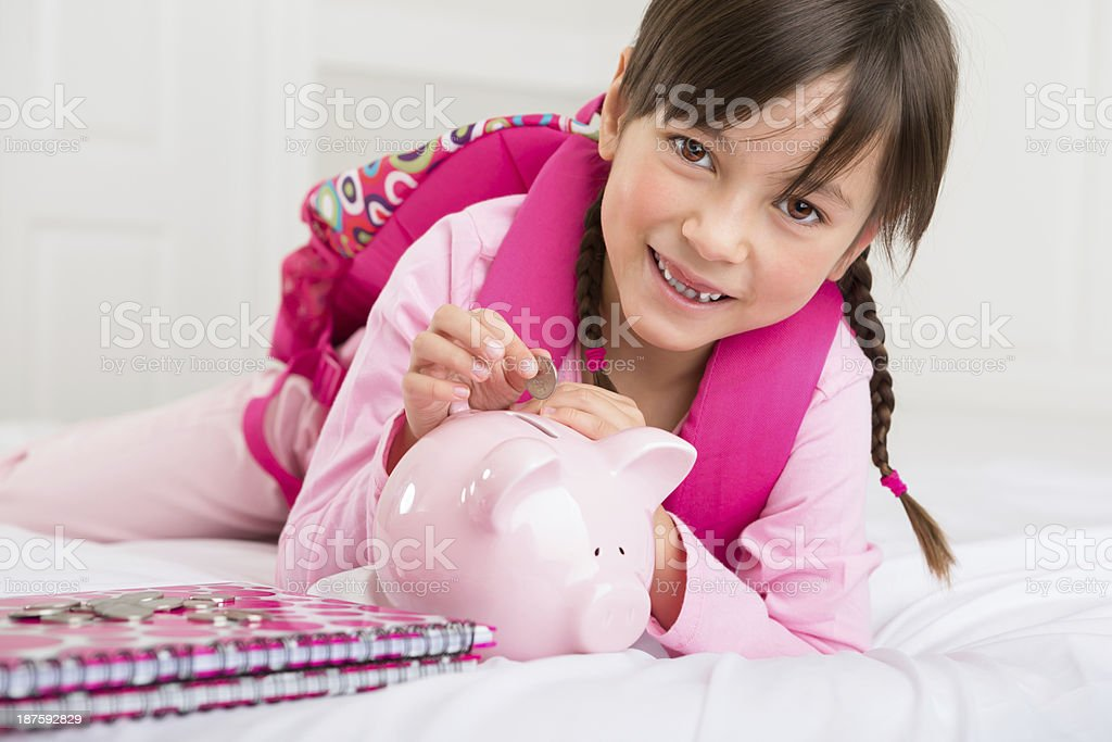 Young girl putting money into her piggy bank royalty-free stock photo