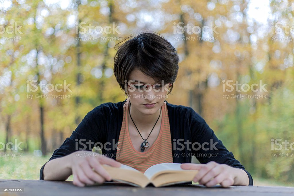 Young girl reading a book in a park royalty-free stock photo