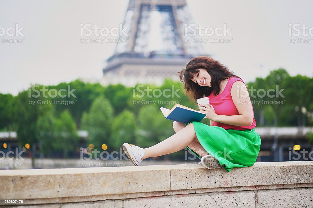 Young girl reading a book near the Eiffel tower stock photo
