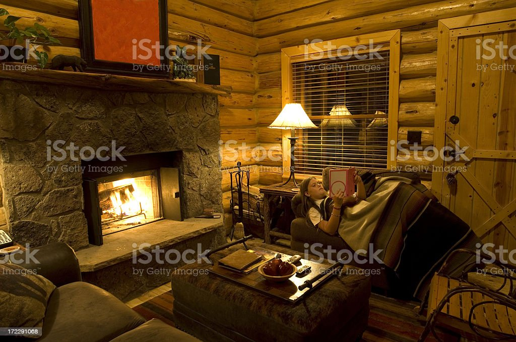 Young girl reading a book next to a fireplace stock photo