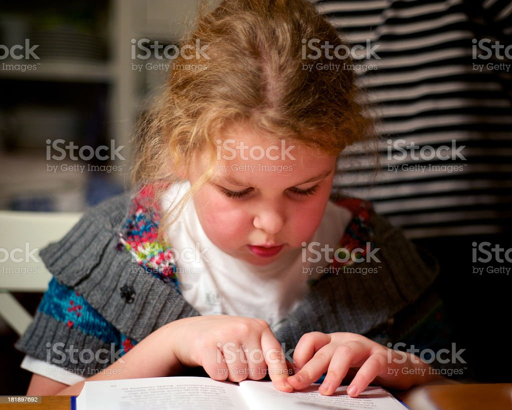 A young girl reading a book with her finger on page stock photo