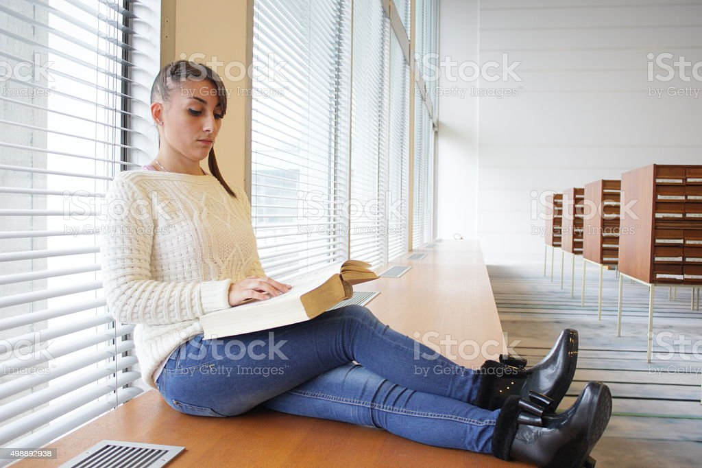 Young girl reading a book within the Library stock photo