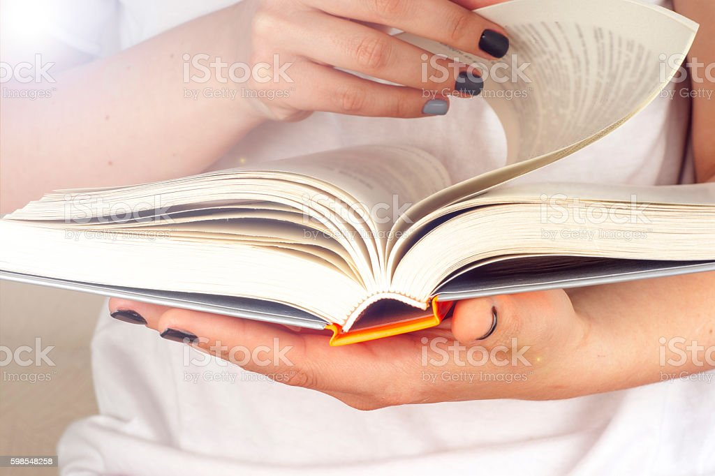 Young girl reading an open old book. Knowledge, stock photo