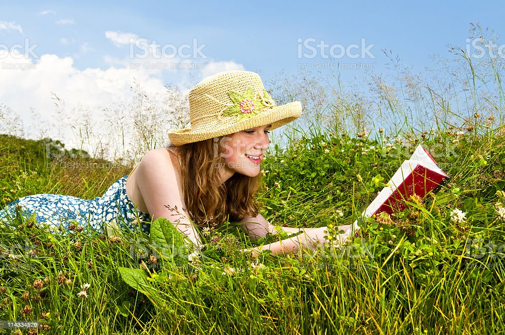 Young girl reading book in meadow royalty-free stock photo