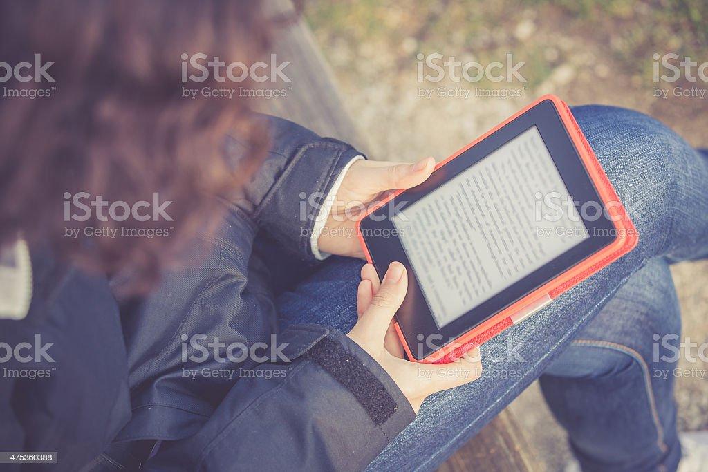 Young Girl Reading E-book at Park stock photo