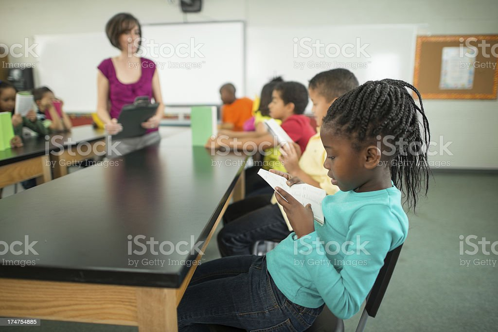 Young girl reading in class. stock photo