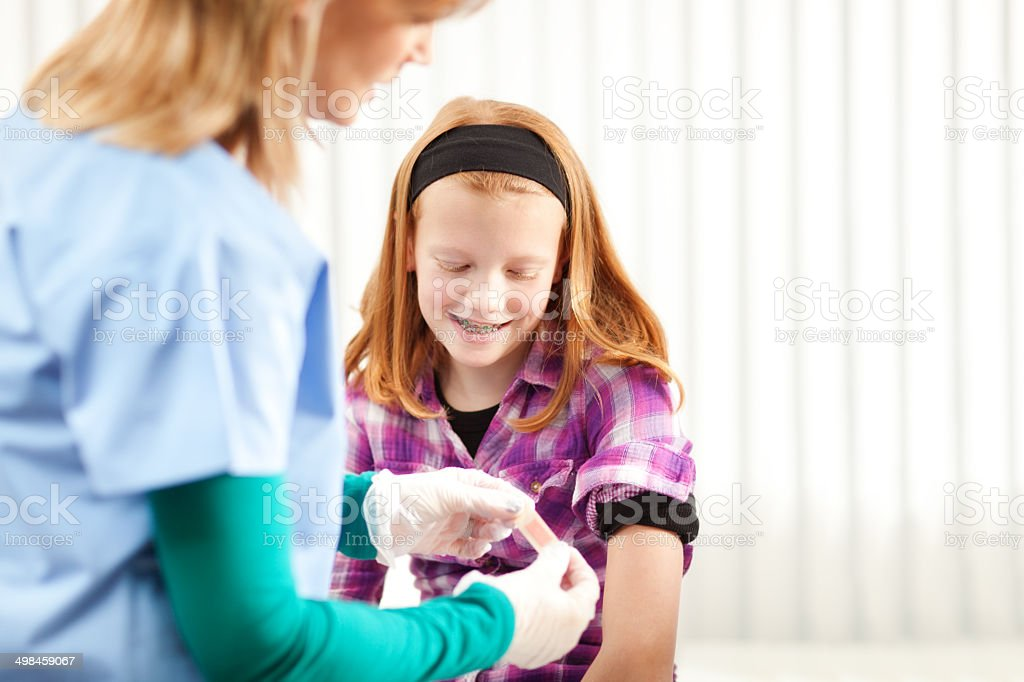 Young Girl Recieving Care in Doctor's Clinic Horizontal stock photo