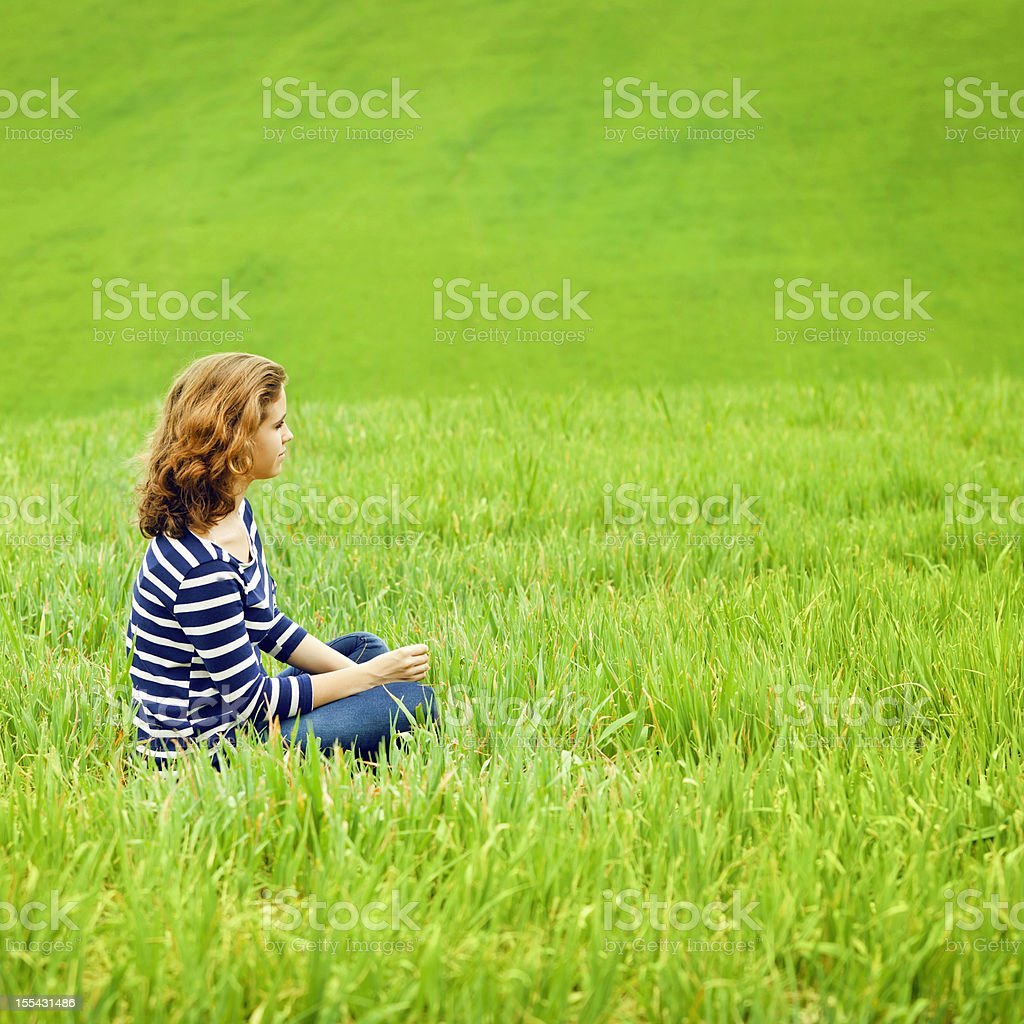 Young girl relaxing on a green field royalty-free stock photo