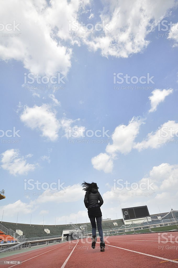 young girl running in stadium royalty-free stock photo