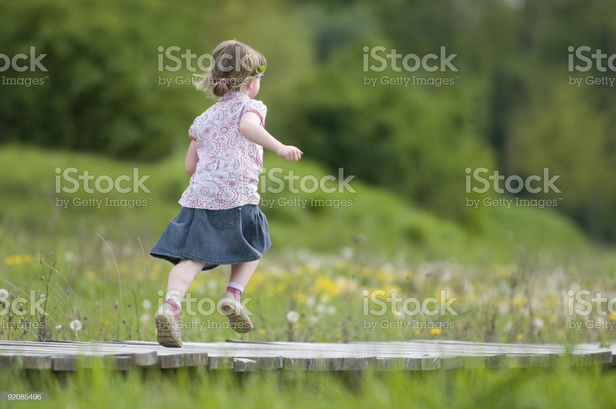 young girl running over a wooden bridge royalty-free stock photo