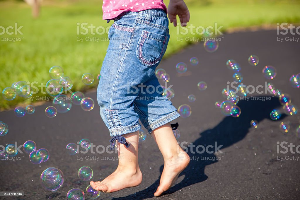 Young Girl Running Through Bubbles stock photo