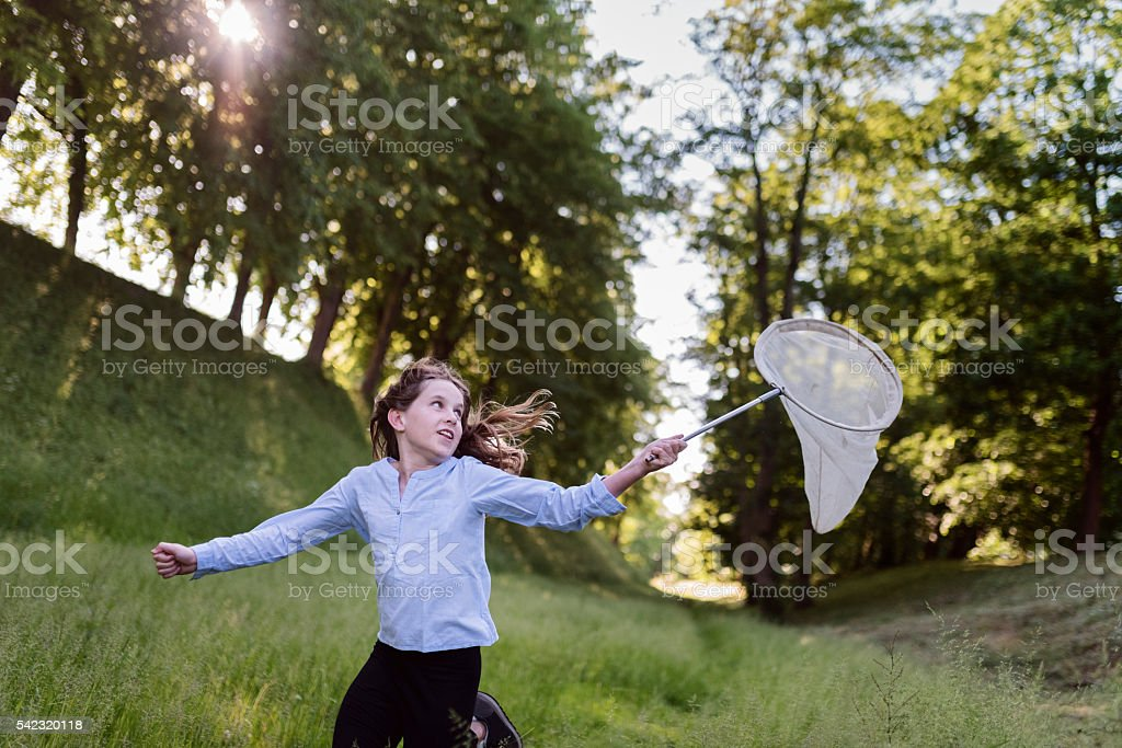 Young Girl Running With a Butterfly Net. stock photo