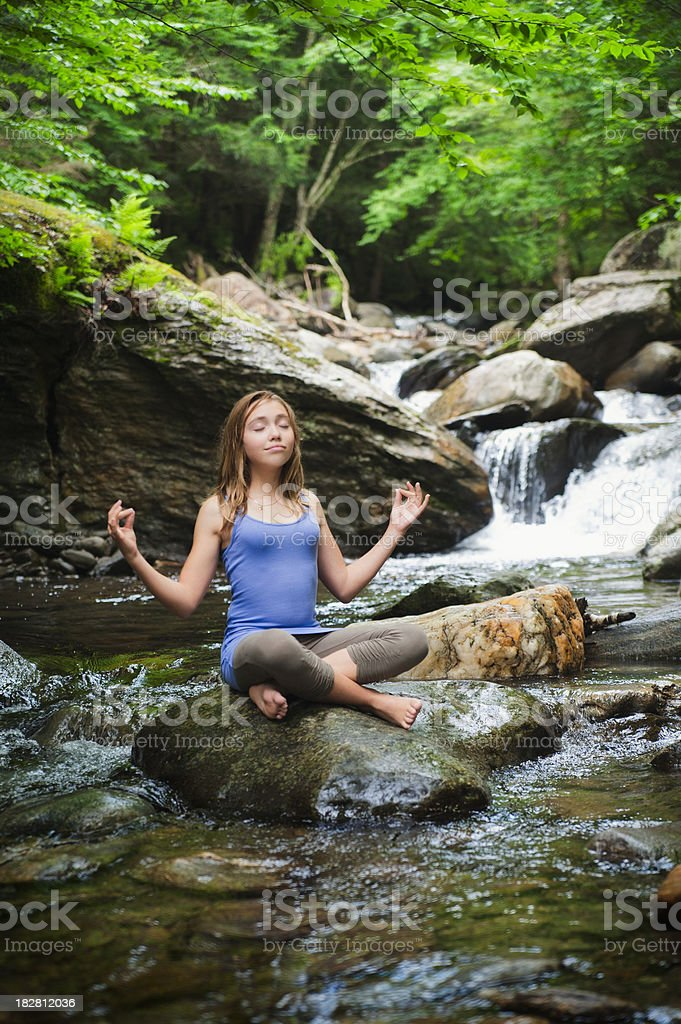 Young Girl Sat Meditating on a Rock by a Waterfall royalty-free stock photo