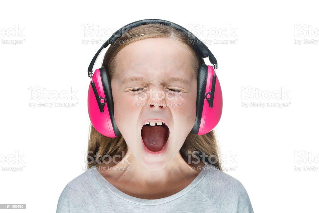 Young girl screaming, wearing pink earmuffs. stock photo