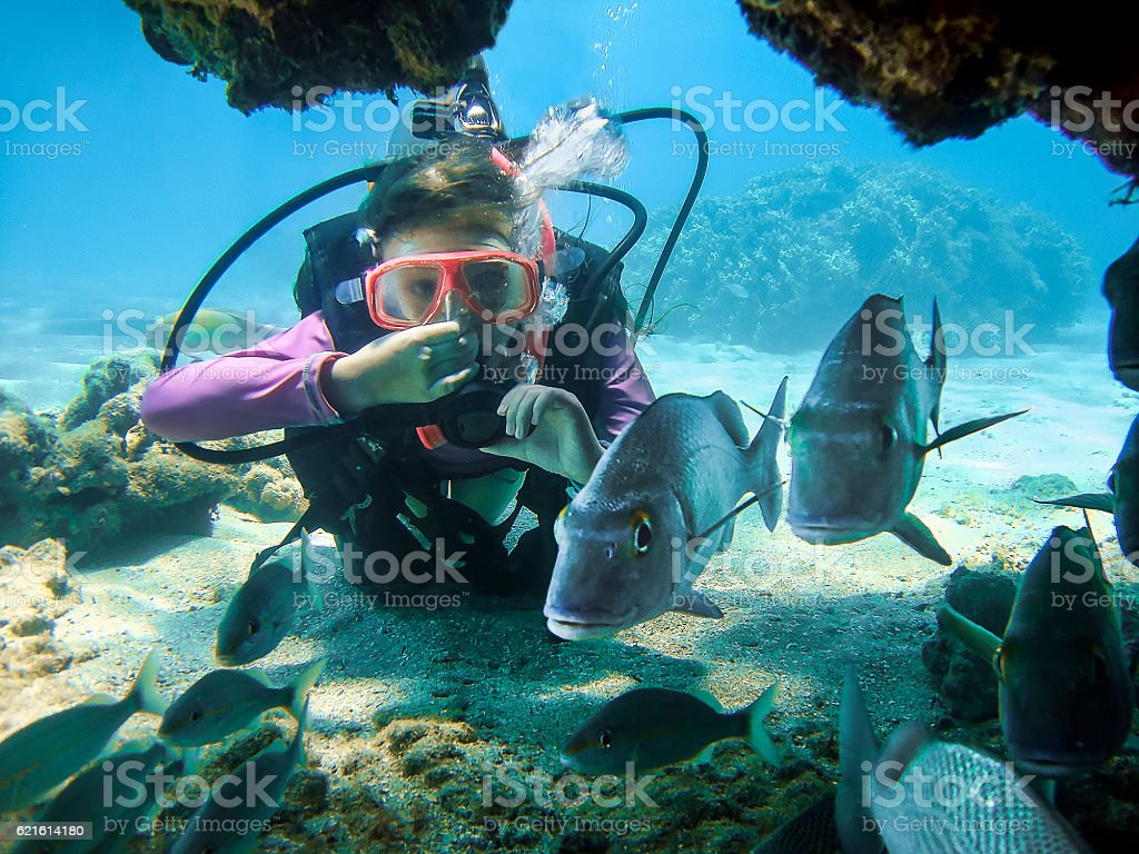 Young Girl Scuba Diving in Clear Water Behind Some Fishes stock photo