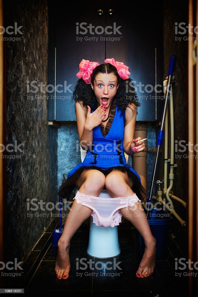 Young girl secretly smoking in toilet. But someone saw her royalty-free stock photo