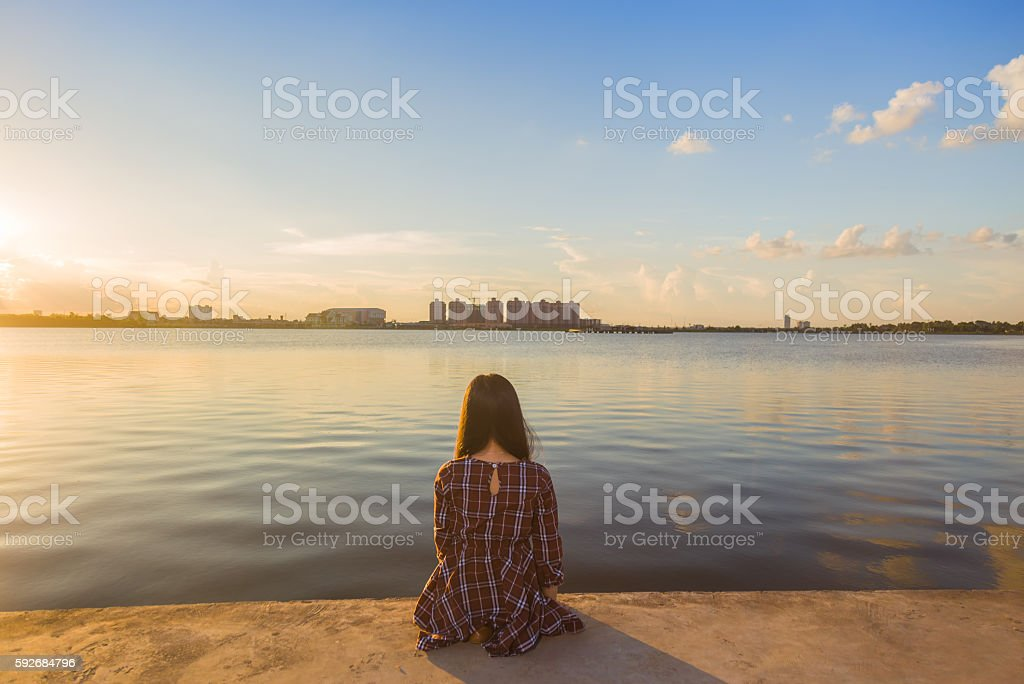 Young girl setting alone sunset stock photo