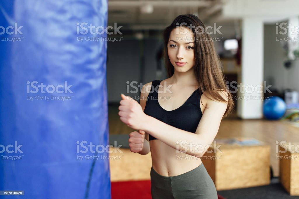 Young girl shnok to the punchball on gym background stock photo