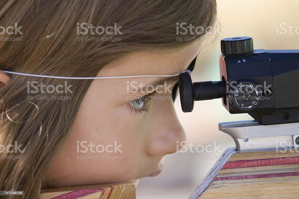 Young girl shooting biathlon rifle stock photo