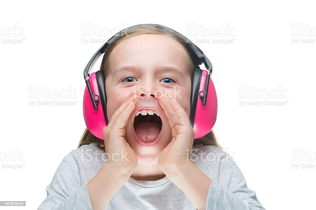 Young girl shouting, wearing pink earmuffs. stock photo
