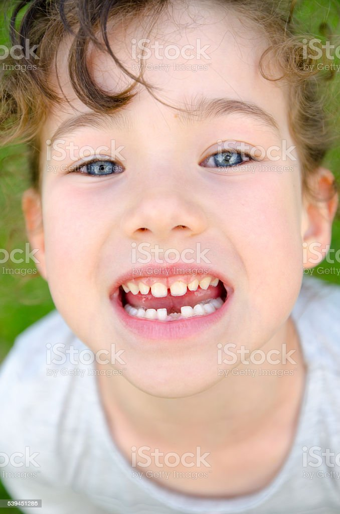 Young girl showing her first tooth that felt stock photo
