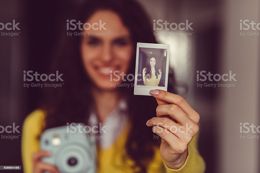 Young girl showing instant self portrait stock photo
