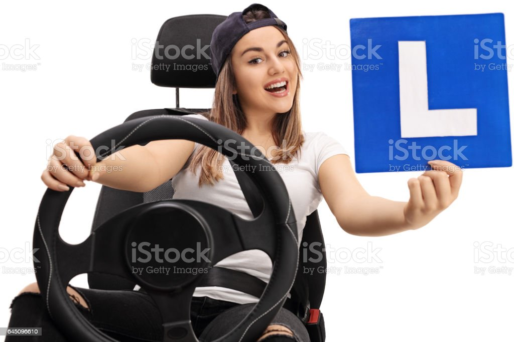 Young girl showing L-sign and sitting in car seat stock photo