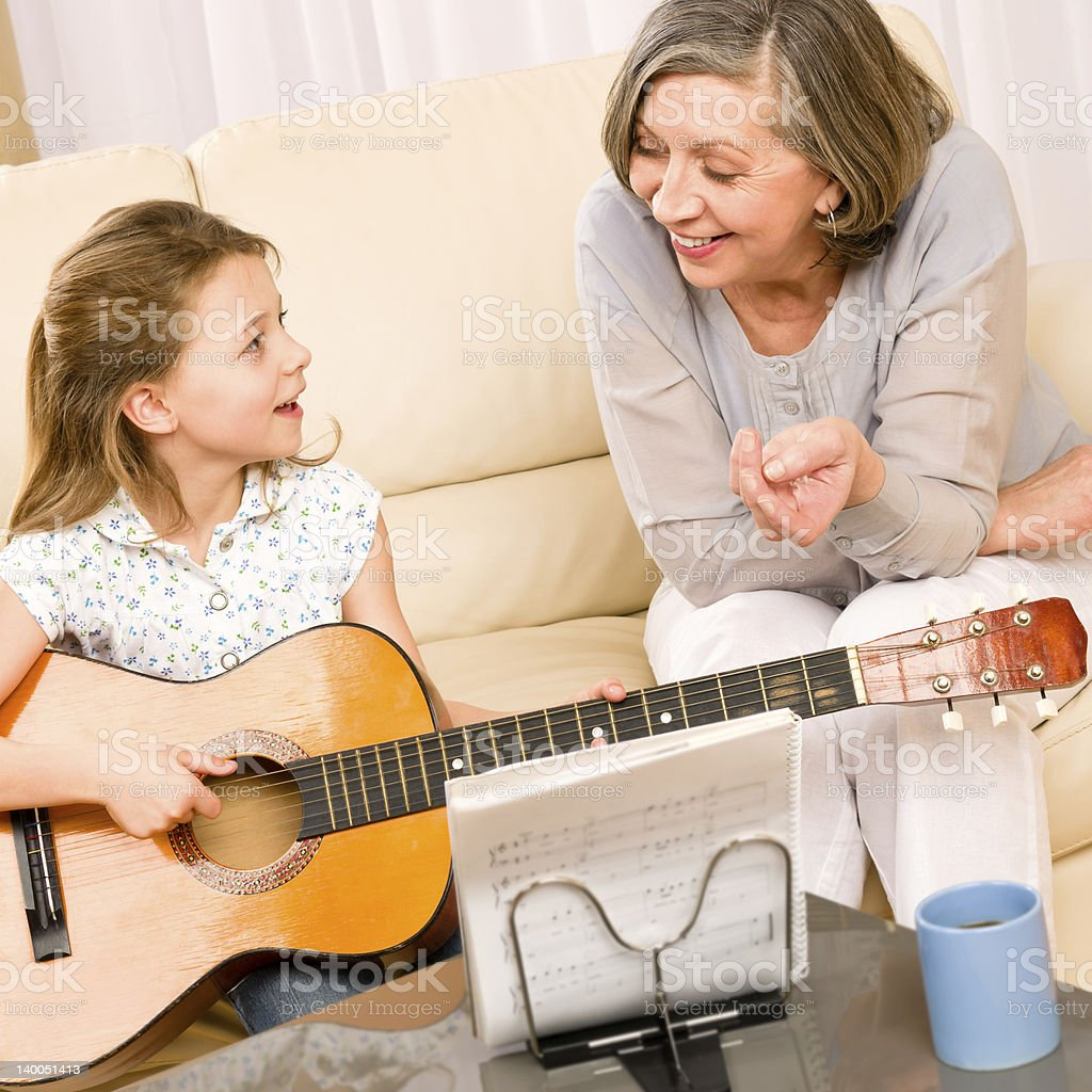 Young girl sing play guitar to grandmother royalty-free stock photo