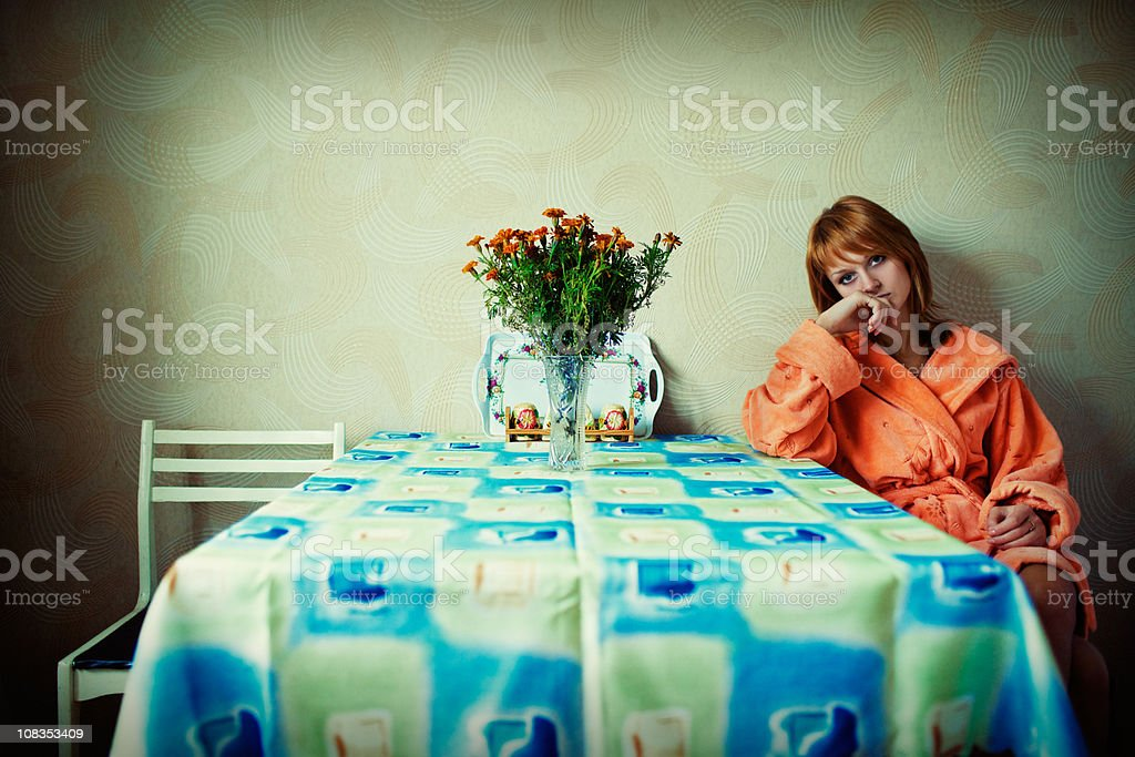Young girl sits alone in the kitchen royalty-free stock photo
