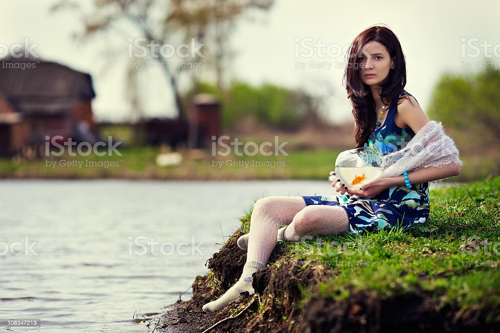 Young girl sits by a pond with goldfish royalty-free stock photo