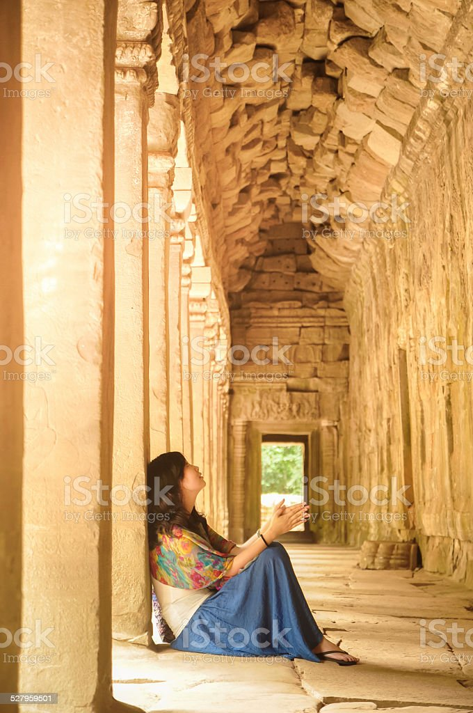 young girl sitting and leaning on ancient pillar in corridor royalty-free stock photo