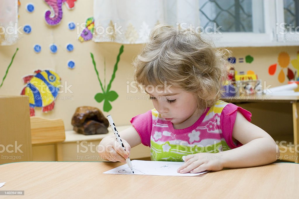 Young girl sitting at a table drawing a picture royalty-free stock photo