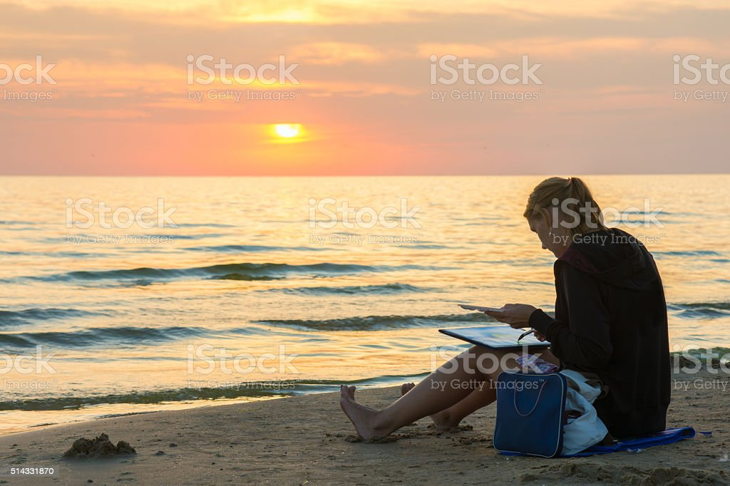 Young girl sitting beach and draw sheet of watercolor sunset stock photo