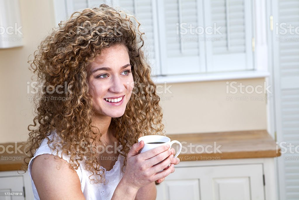 Young girl sitting drinking a cup of coffee at home royalty-free stock photo