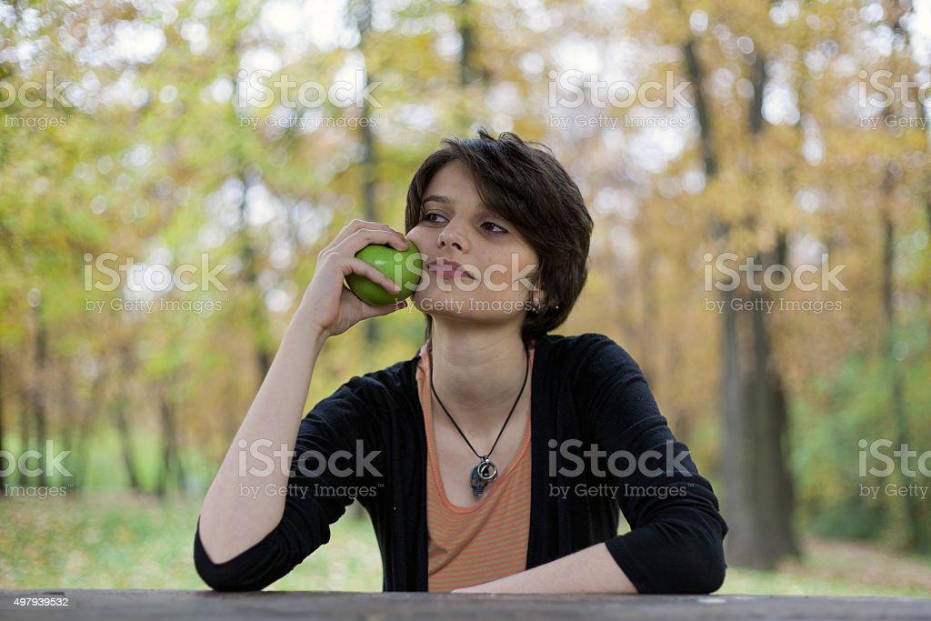 Young girl sitting in a park and holding an apple royalty-free stock photo