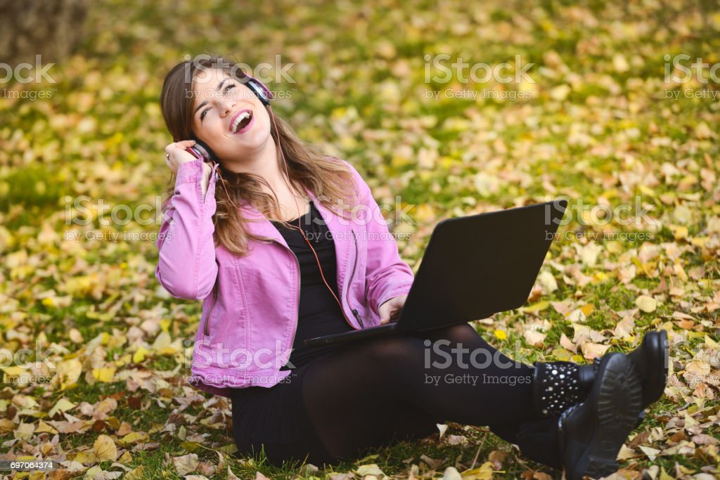 Young girl sitting in a park, listening music and chatting stock photo