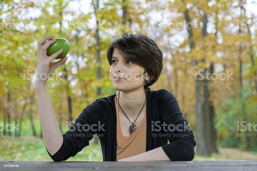 Young girl sitting in a park, looking at apple royalty-free stock photo