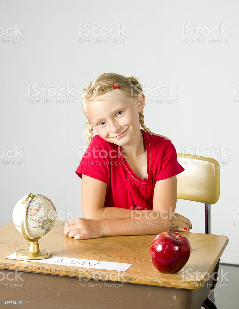 Young girl sitting in class with and apple stock photo
