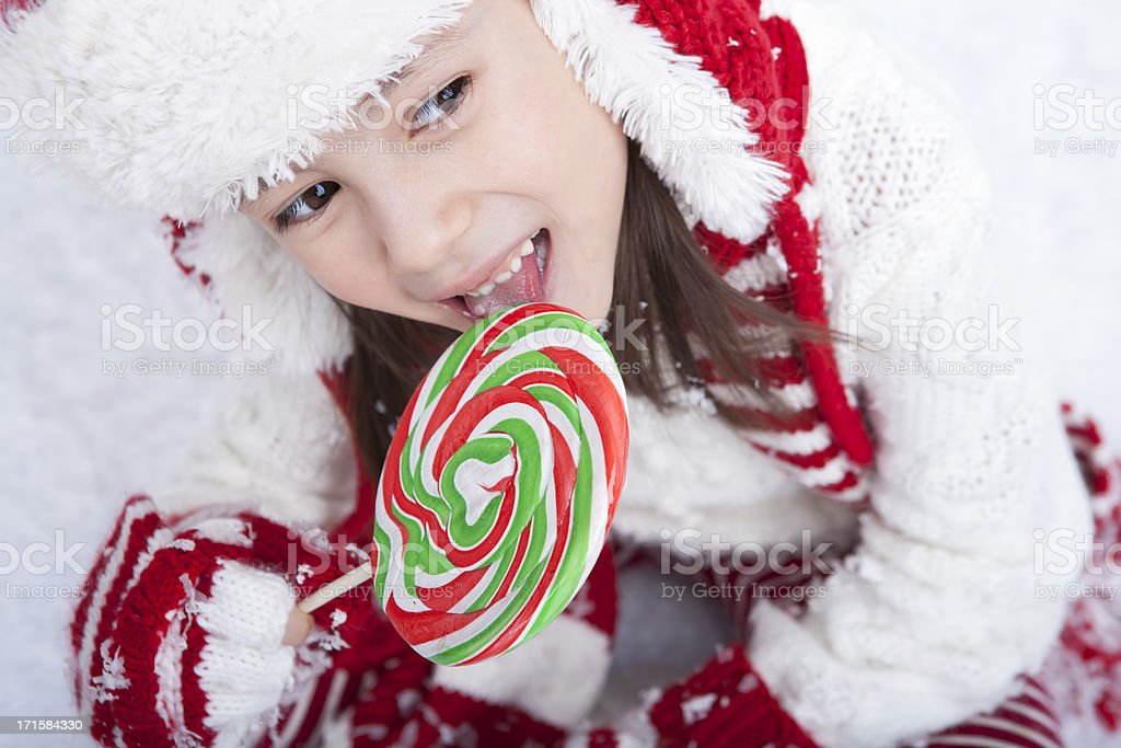 Young girl sitting in the snow eating candy royalty-free stock photo