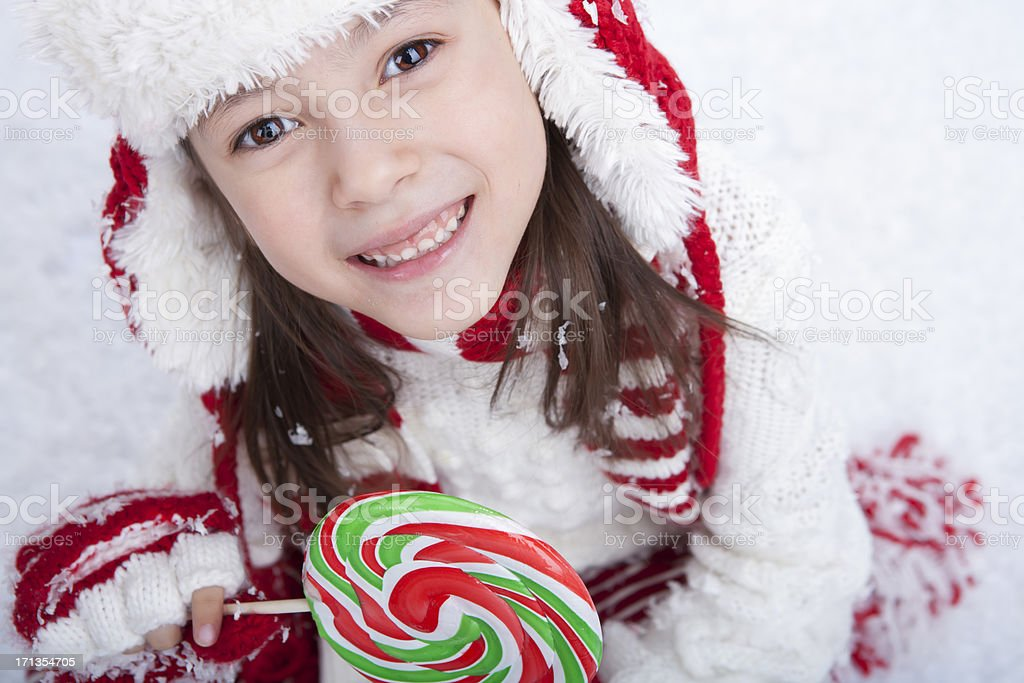 Young girl sitting in the snow with candy royalty-free stock photo
