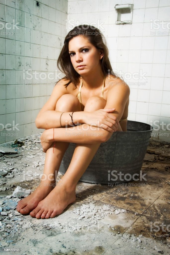 Young Girl Sitting Inside Antique Wash Tub in Ruined Bathroom stock photo