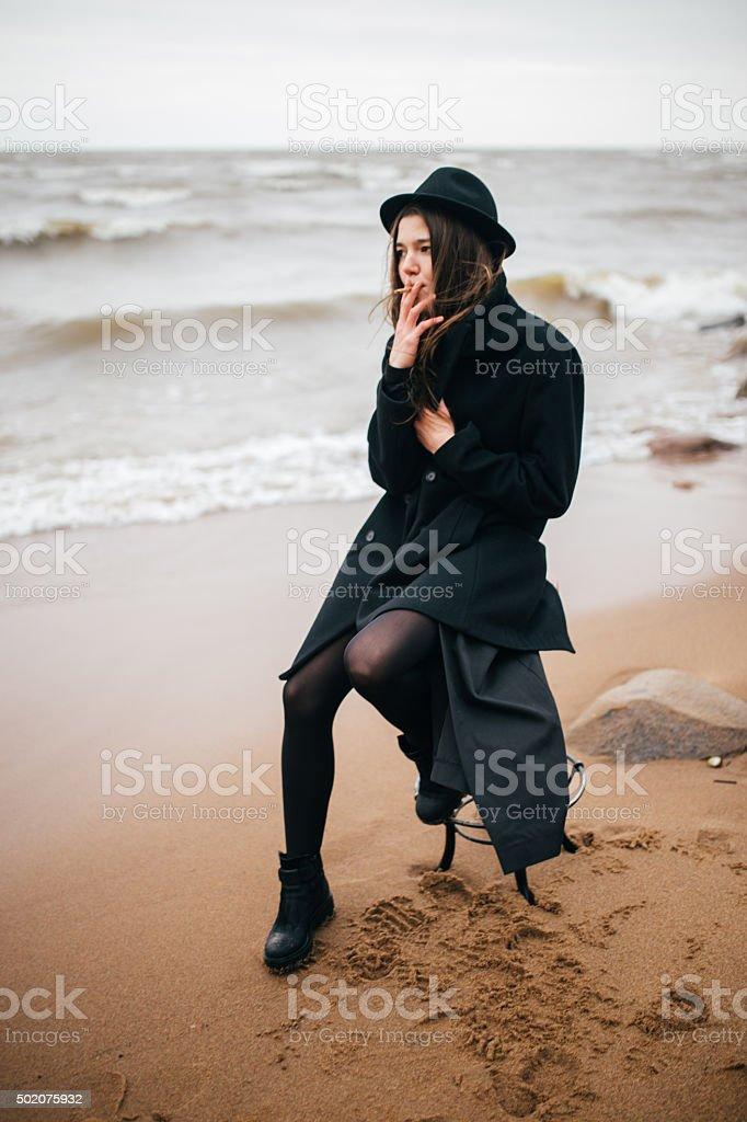 Joven sentada en una silla y smokes foto de stock libre de derechos