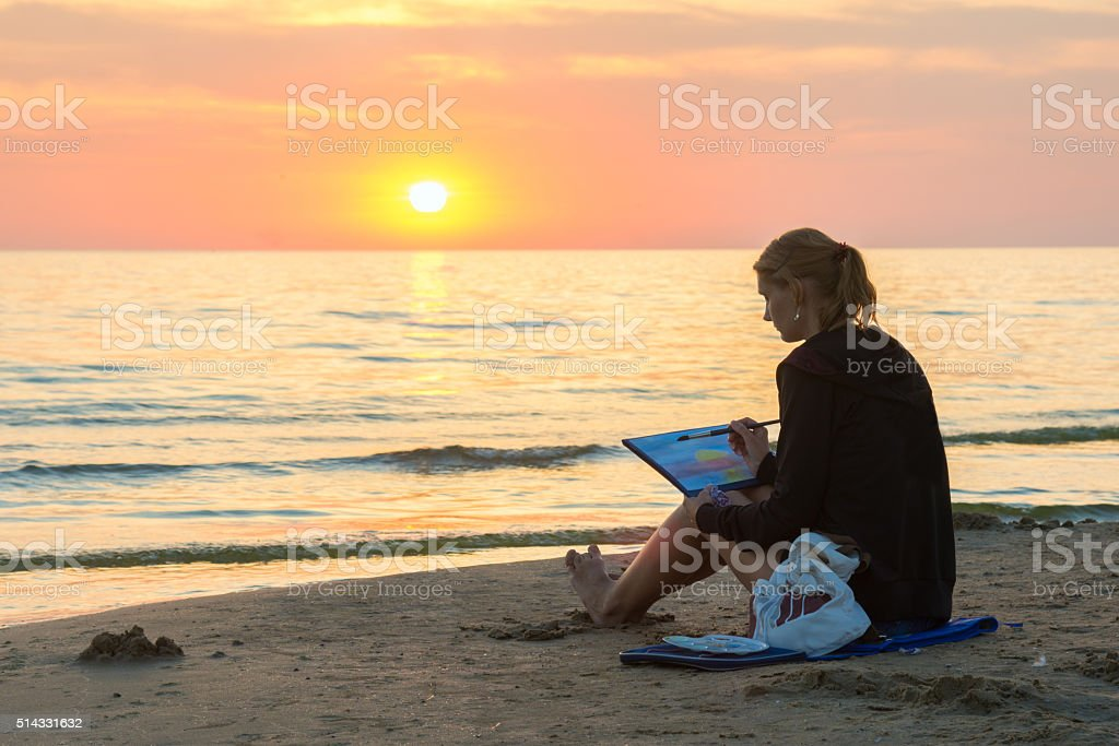 Young girl sitting on beach and draw sheet watercolor sunset stock photo