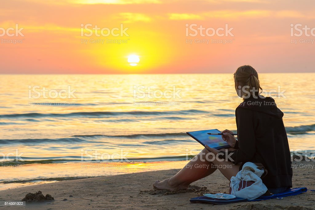 Young girl sitting on beach, drawing sheet of watercolor sunset stock photo
