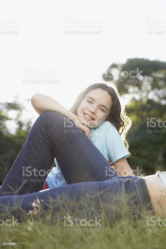 Young girl sitting on grass outdoors smiling with woman lying in front of her royalty-free stock photo