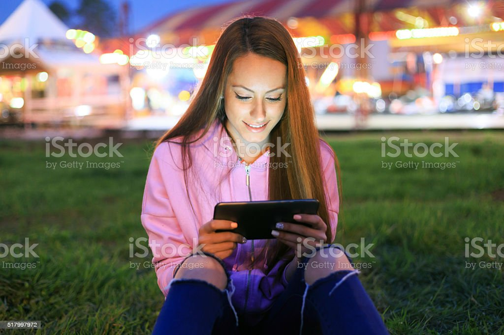 Young girl sitting on grass using digital tablet stock photo