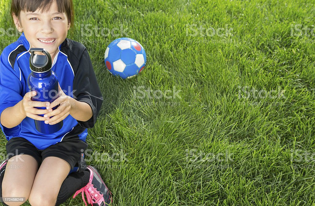 Young girl sitting on her soccer ball taking a drink royalty-free stock photo