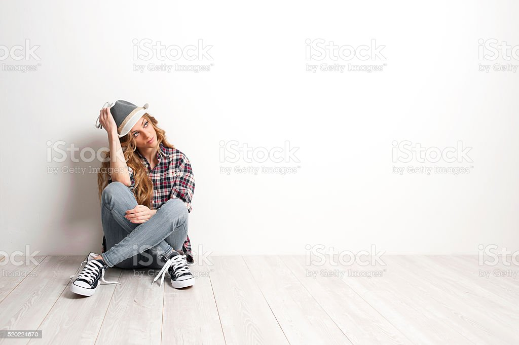 Young girl sitting on the floor at home stock photo